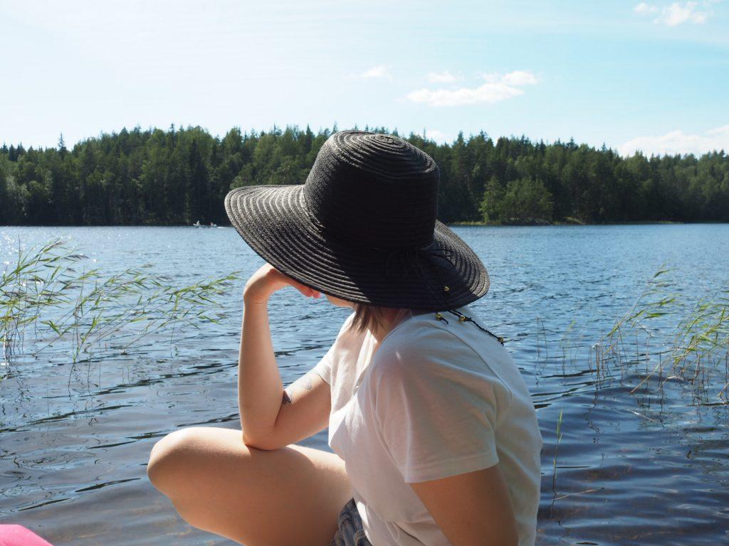 Hattupäinen nainen katsoo järvelle aurinkoisena päivänä.