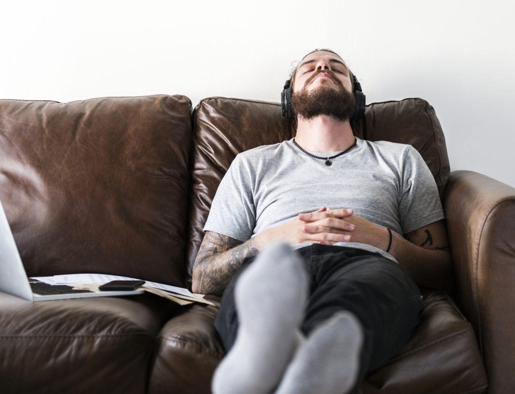 Mies makaa sohvalla kuulokkeet päässä.