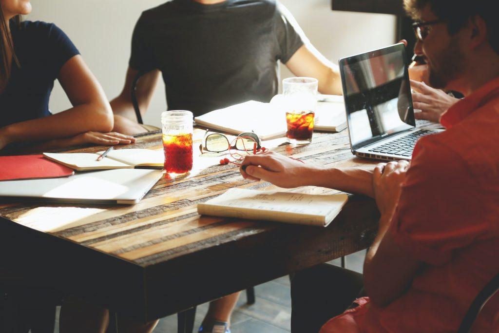 Lähikuva pöydän ääressä istuvista ihmisistä. Pöydällä on avonaisia muistivihkoja, läppäri ja juomalaseja.