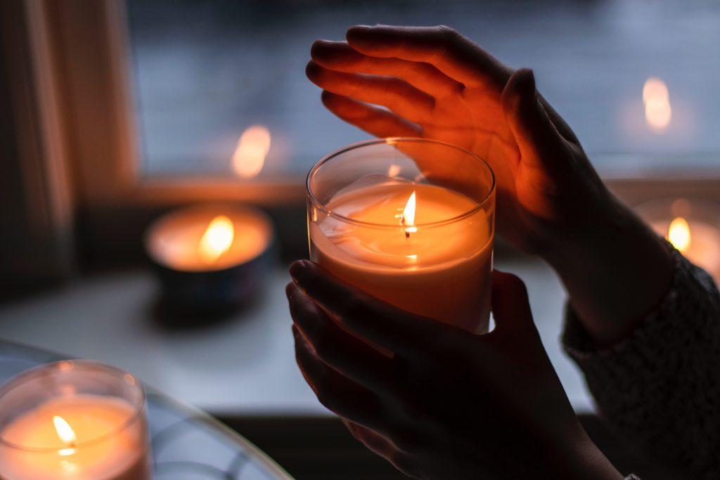 Henkilö pitää toisessa kädessään palamassa olevaa kynttilää ja suojaa toisella kädellä kynttilän liekkiä.