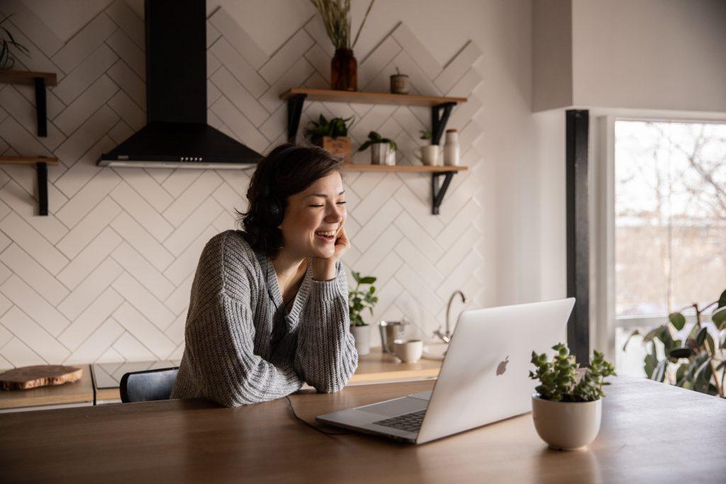 Nainen istuu keittiössä kannettavan tietokoneen edessä ja katsoo hymyillen tietokoneen näyttöä.