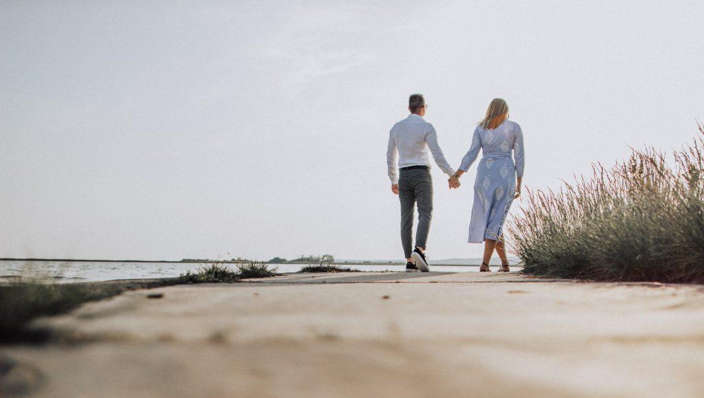 Mies ja nainen kävelevät käsikädessä pois päin kamerasta.