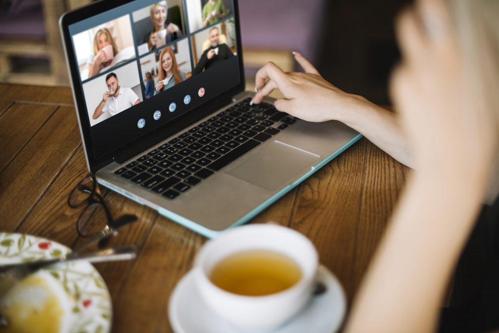 kannettavan tietokoneen äärellä kahvikupin kera