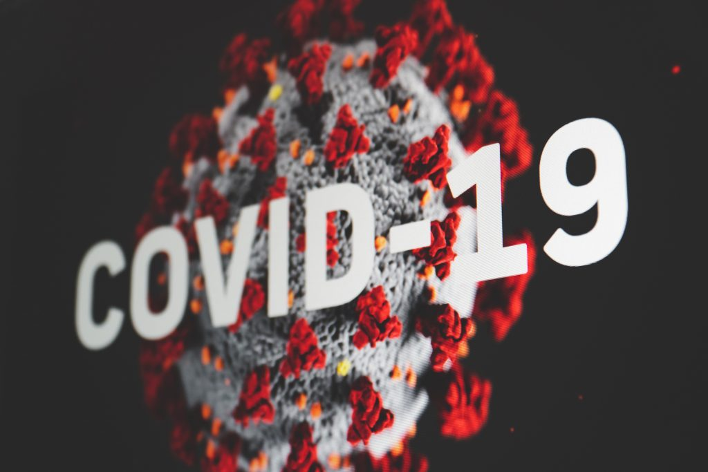 Lähikuva viruksesta, jonka päällä teksti Covid-19