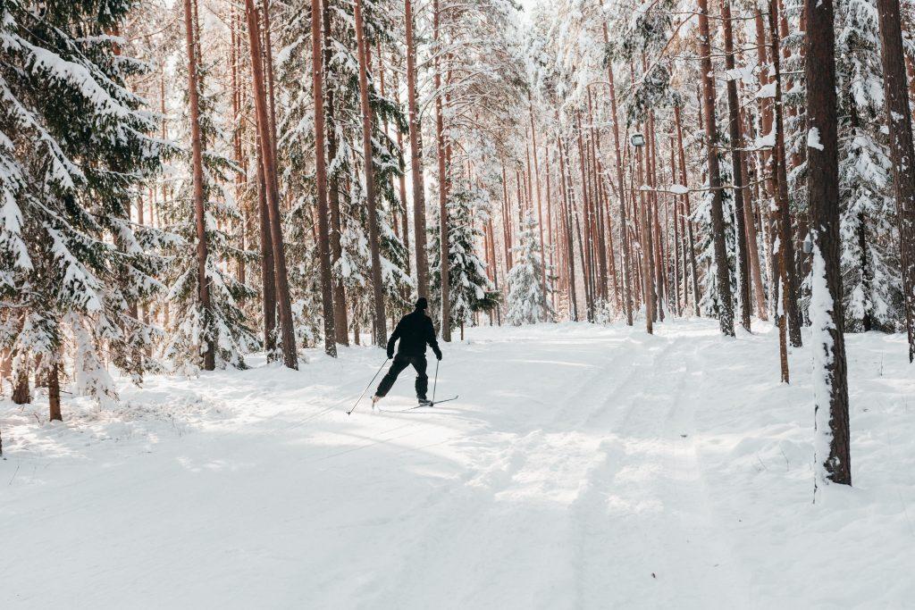 Mies mustassa asussa hiihtää lumisessa metsässä.