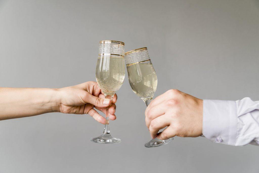 Kaksi henkilöä kilistelee laseja, joissa on kuohuviinin näköistö juomaa