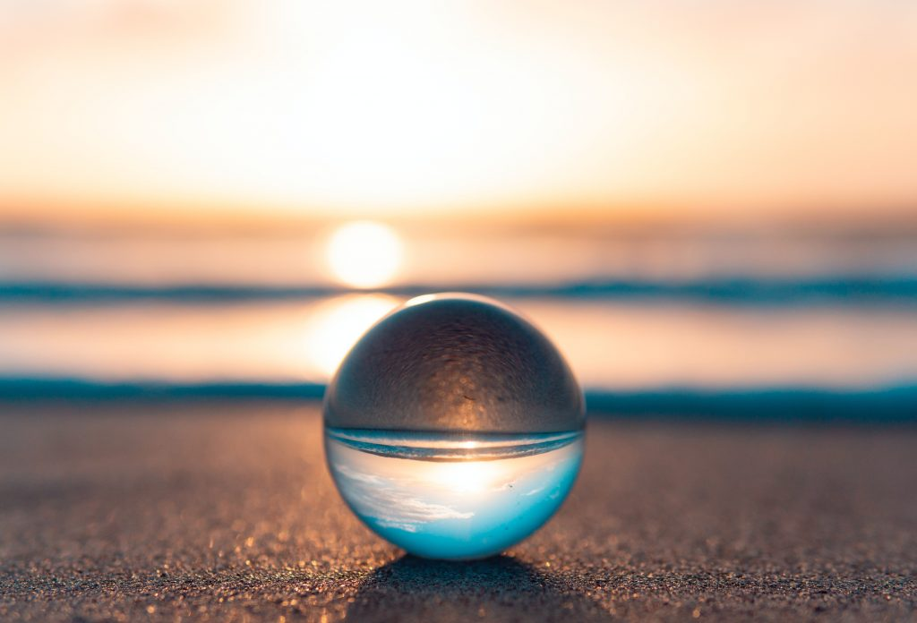 Lasinen pallo rannalla auringonlaskun aikaan. Taustalla näkyy meri.