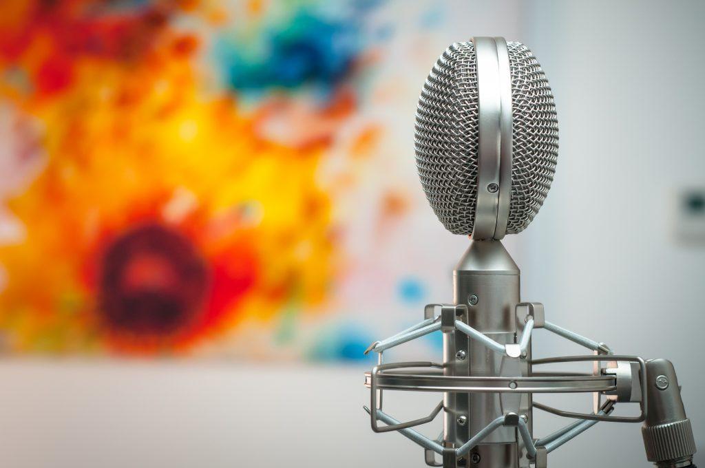 Harmaa mikrofoni värikkään taustan edessä